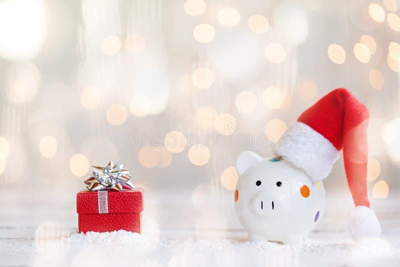 Chapeau rouge de Santa avec la tirelire et présent sur le fond de lumière de bokeh photo libre de droits
