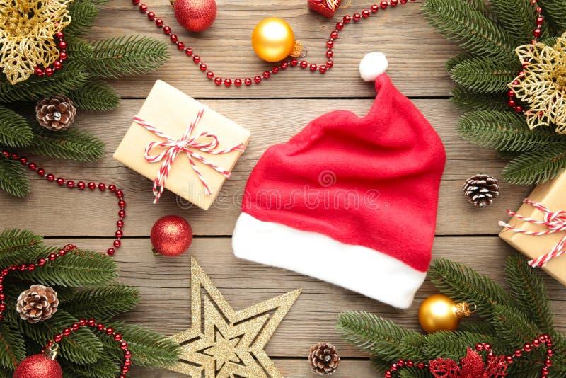 Chapeau rouge du Père Noël et cadeaux sur fond gris Décoration de Noël photographie stock