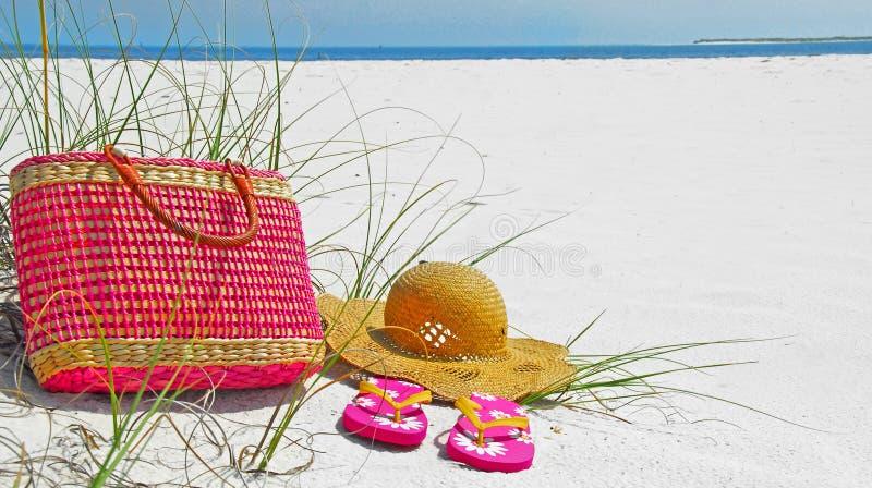 Chapeau, sac, et santals sur la plage photos libres de droits