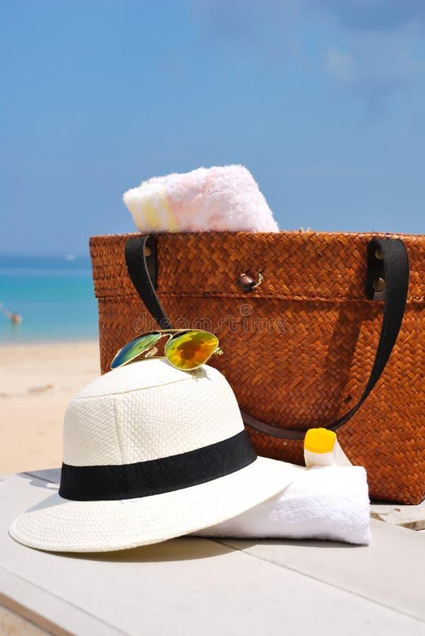 Chapeau, sac, verres de soleil et serviette sur une plage tropicale photos libres de droits