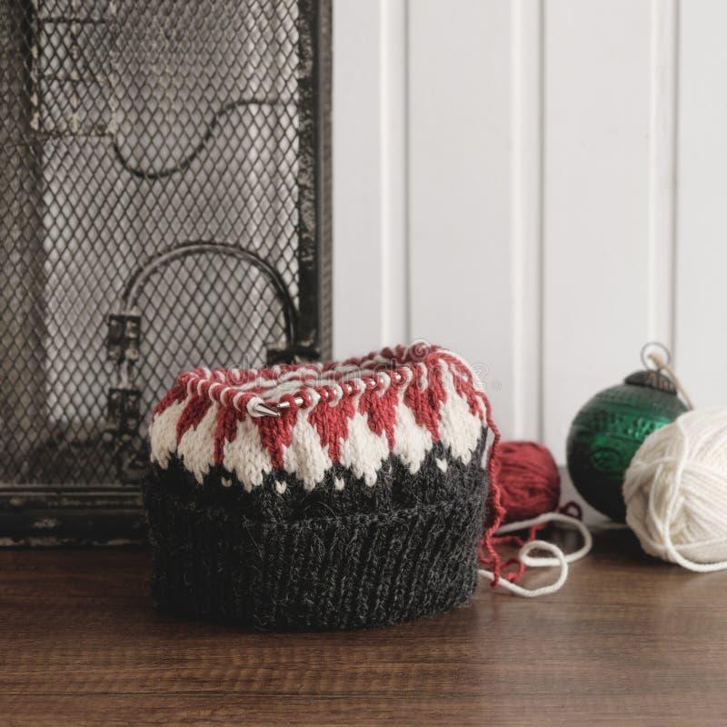 Chapeau tricoté non fini sur des aiguilles de tricotage image libre de droits