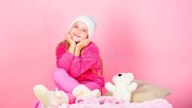 Chapeau tricoté par fille d'enfant Concept d'accessoire d'hiver Long fond de rose de rêve de cheveux de fille Chapeau tricoté par photo libre de droits