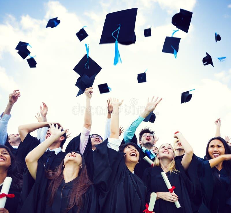 Chapeaux d'obtention du diplôme jetés dans le ciel image stock