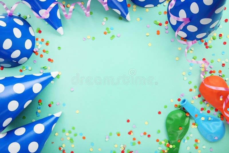 Chapeaux de papier avec des ballons et des confettis photographie stock libre de droits