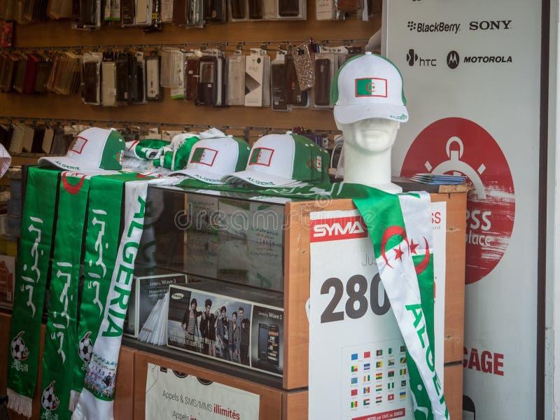 Chapeaux et écharpes de défenseurs du football avec les couleurs de l'Algérie sur l'affichage dans un magasin français possédé pa photo stock