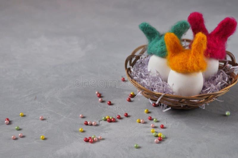 Chapeaux faits main lumineux de lapin de Pâques pour des oeufs de laine dans un panier en osier sur un fond concret gris Décorati photographie stock libre de droits