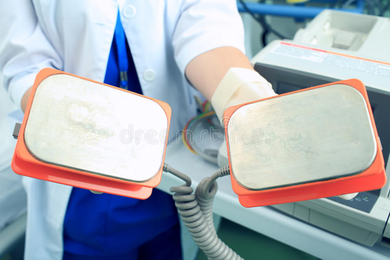 Chapeia o desfibrilador nas mãos do doutor imagens de stock royalty free