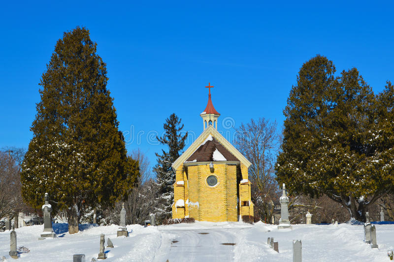 Chapel in Cemetery. A beautiful chapel in a cemetery in Burlington, Wisconsin with snow on the ground and some on the roof. Racine County - United States of stock image