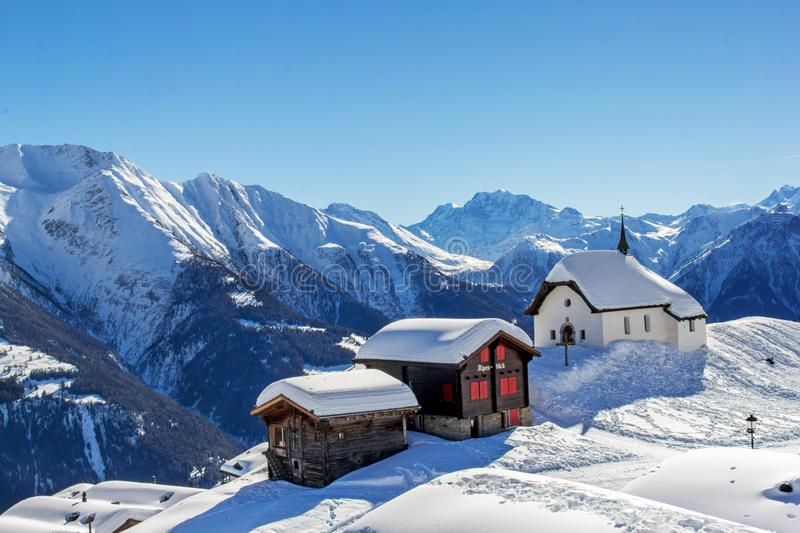 Chapel Maria in Snow Kapelle zum Schnee with two old chalets. The landmark architecture in the Swiss alps village Bettmeralp in Canton Vaud. It is one of the royalty free stock photography