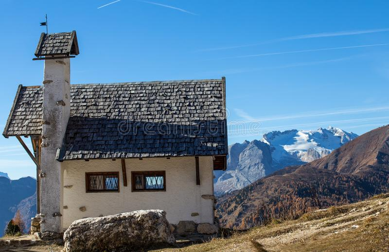 Chapel with Marmolada mountain in background on Falzarego Pass Passo di Falzarego at sunny autumn day. Dolomites Alps, Italy. royalty free stock photo