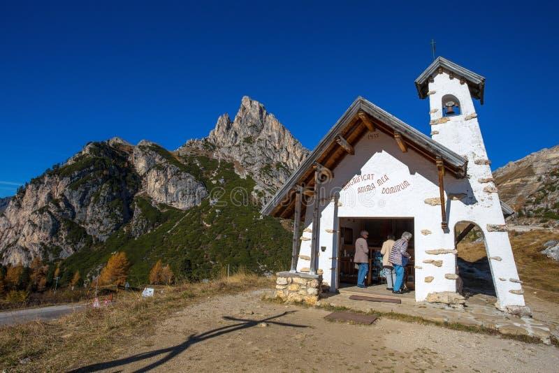 Chapel with Sass de Stria mountain in background on Falzarego Pass Passo di Falzarego at sunny autumn day. Dolomites Alps, Italy royalty free stock images