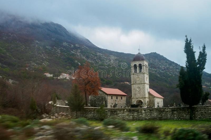 A chapel in a small village cemetery behind a fence in the background of mountains in cloudy weather. The foreground is blurred stock photography