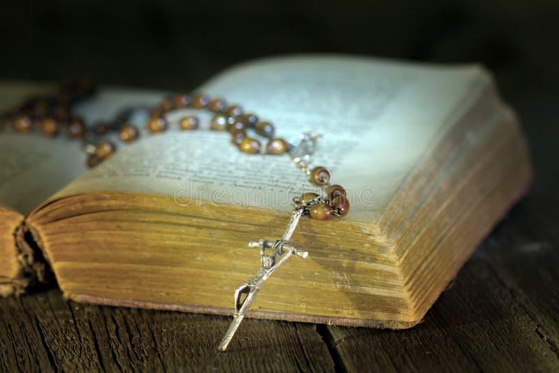 Chapelet et bible sur la table en bois de vintage par nuit photographie stock