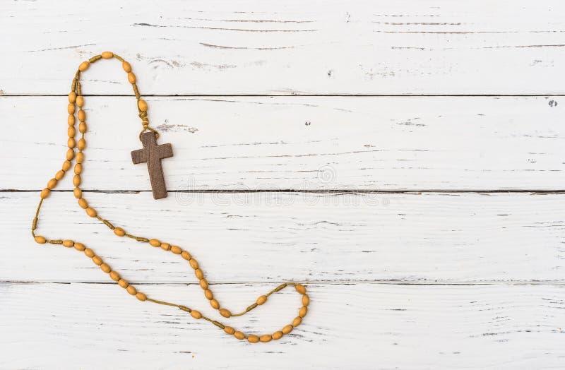 Chapelet et perles croisés en bois sur le fond en bois blanc image stock