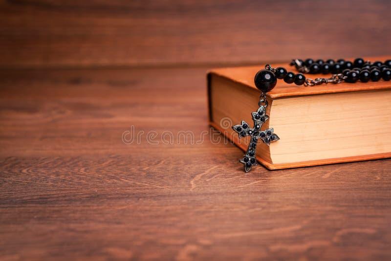 Chapelet sur la bible à la table en bois photographie stock