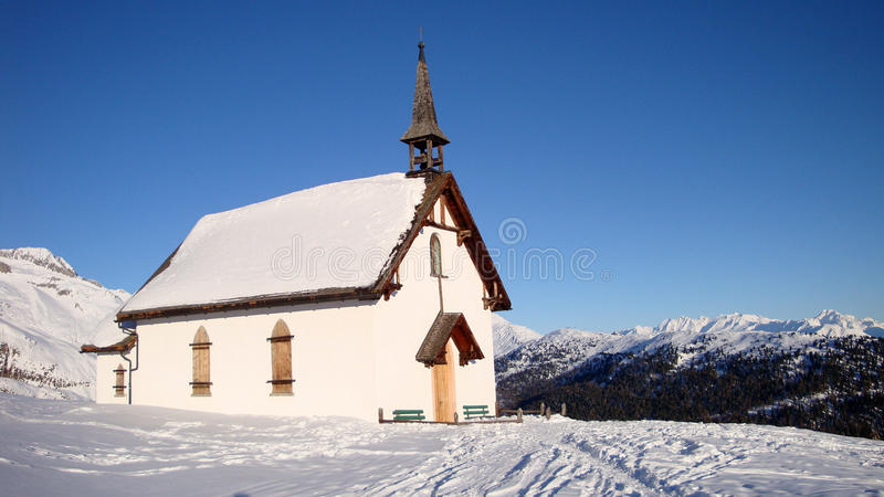 Chapelle dans la neige dans les alpes autrichiennes photo stock