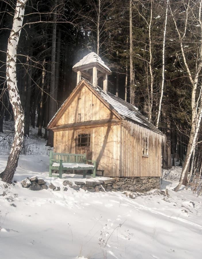 Chapelle en bois avec le banc dans la forêt d'hiver photos stock
