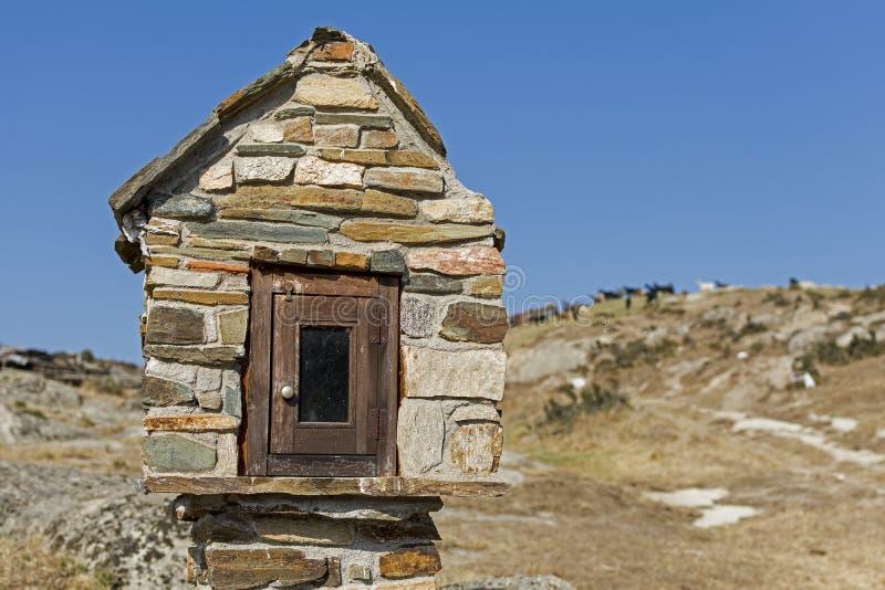 Chapelle miniature de bord de la route avec des chèvres à l'arrière-plan photo stock
