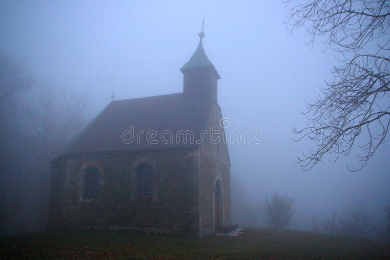 Chapelle sur la colline brumeuse images stock