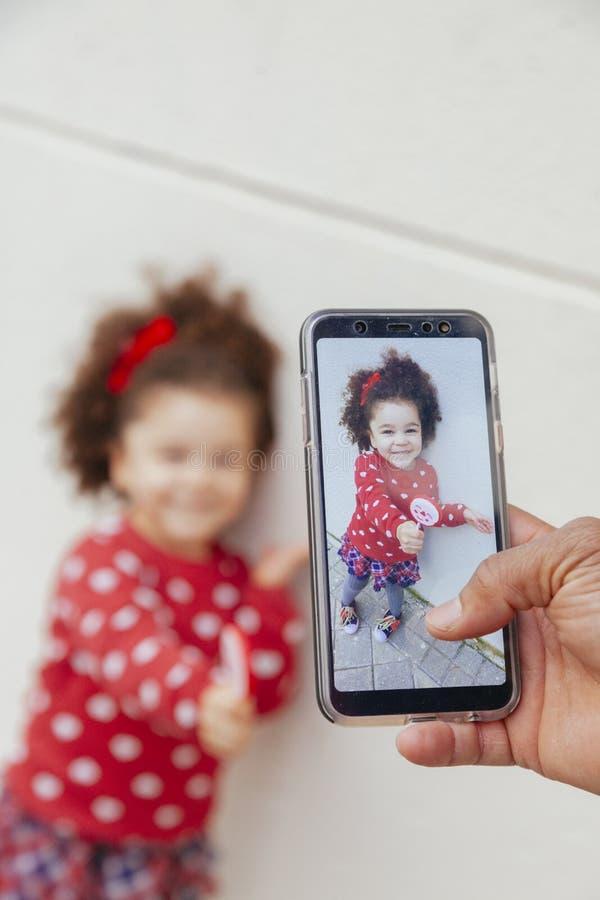 Chapie strza? dziewczyna z smartphone troszk? zdjęcie royalty free