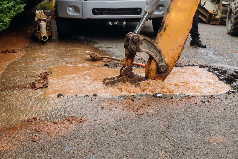 Chapinhar da água de tubulação quebrada a estrada principal imagens de stock