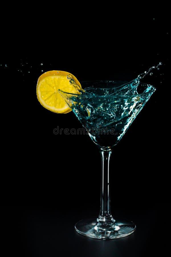 Chapoteo azul de la bebida del agua del cóctel en el vidrio con el limón aislado en negro fotografía de archivo