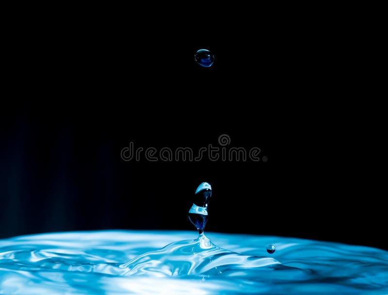 Chapoteo colorido del descenso del agua - gotita de agua en fondo oscuro - gotita de agua azul de océano fotografía de archivo libre de regalías