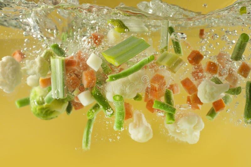 Chapoteo de las verduras en la sopa del agua que cocina concepto fotos de archivo