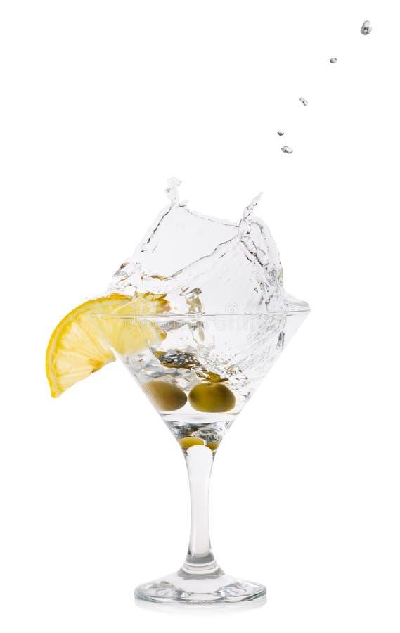 Chapoteo de Martini con las aceitunas en un vidrio de cóctel fotos de archivo