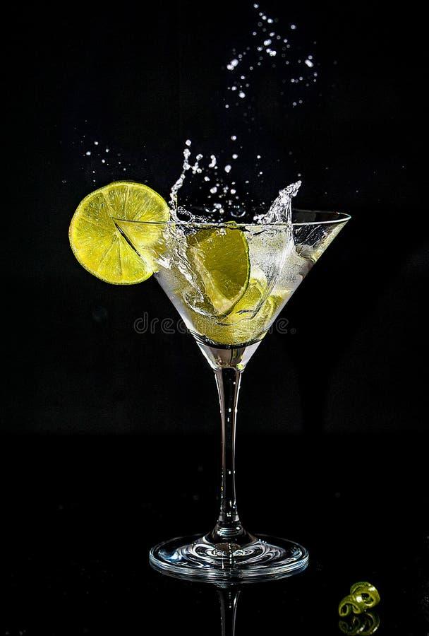 Chapoteo de un cóctel en el vidrio de martini fotos de archivo libres de regalías