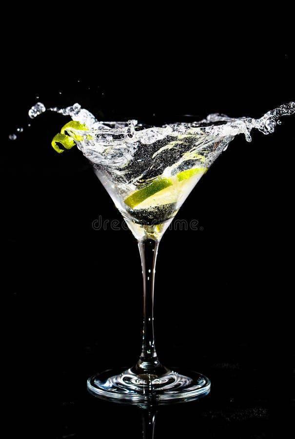 Chapoteo de un cóctel en el vidrio de martini imagen de archivo
