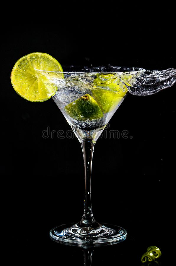Chapoteo de un cóctel en el vidrio de martini fotos de archivo