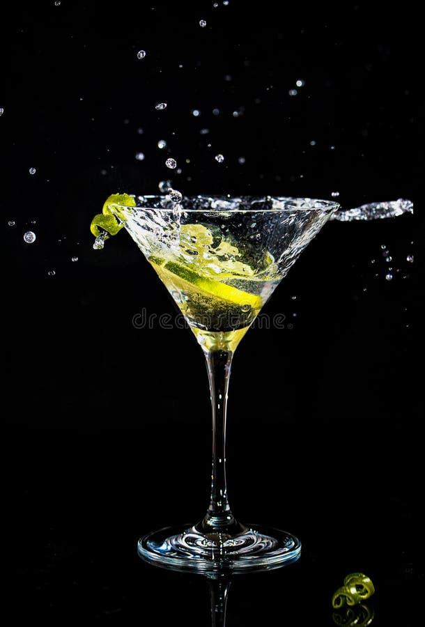 Chapoteo de un cóctel en el vidrio de martini fotografía de archivo libre de regalías