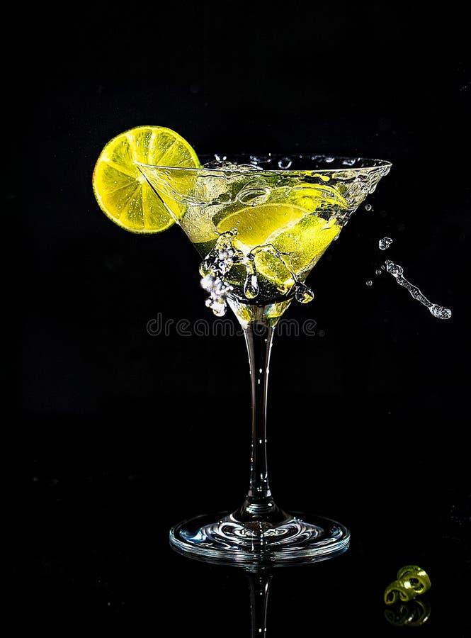 Chapoteo de un cóctel en el vidrio de martini fotografía de archivo