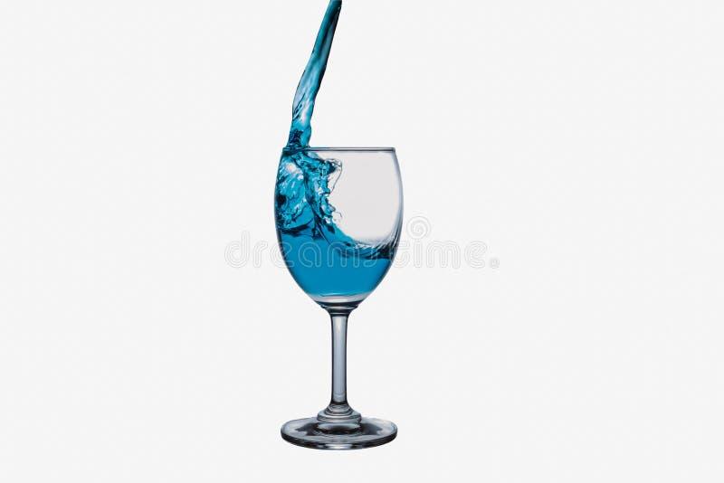 Chapoteo del agua azul en la copa de vino imágenes de archivo libres de regalías