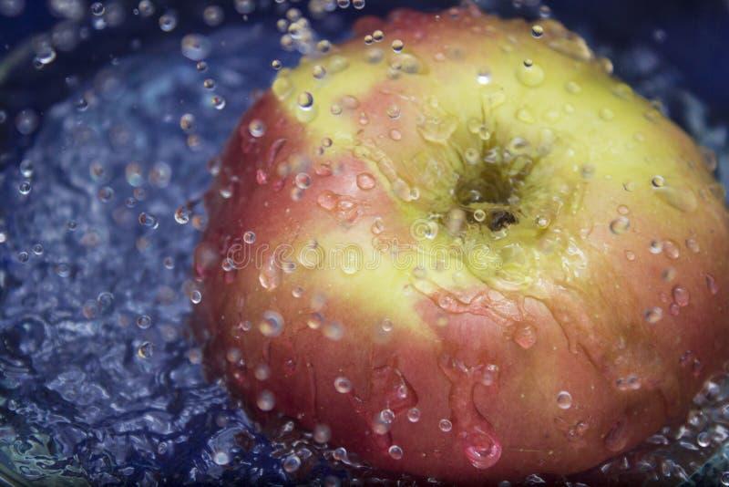 Chapoteo del agua dulce en manzana roja imagen de archivo libre de regalías