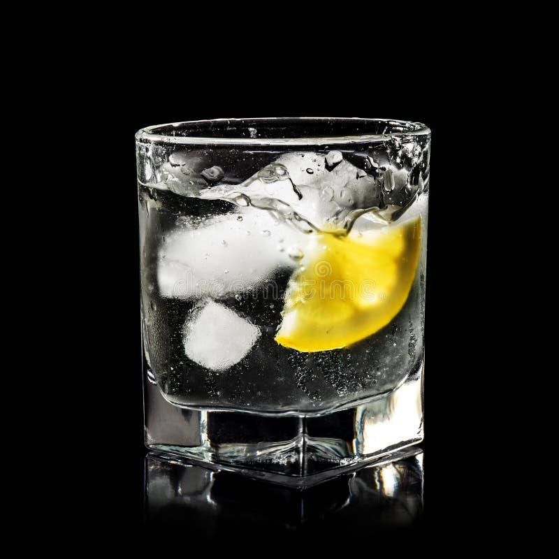chapoteo del agua en el vidrio para el alcohol con hielo puro y el limón amarillo imagenes de archivo