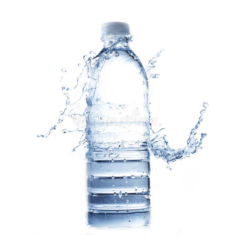 Chapoteo del agua en la botella de agua en blanco foto de archivo