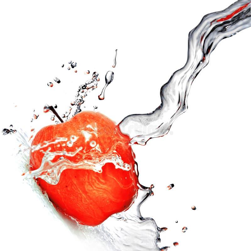 Chapoteo del agua en manzana roja foto de archivo