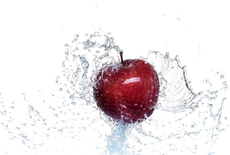 Chapoteo del agua en una manzana roja En el fondo blanco foto de archivo libre de regalías