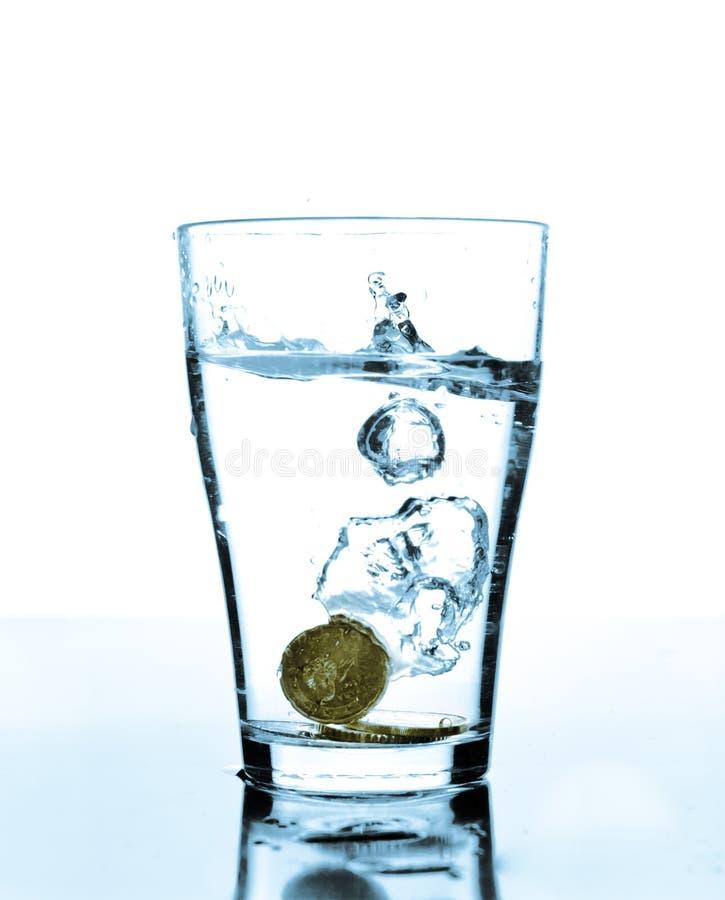 Chapoteo del agua y de las monedas en un vidrio fotos de archivo libres de regalías