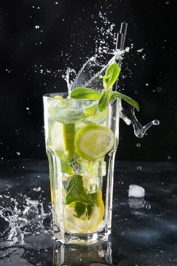 Chapoteo del cóctel o de la limonada del mojito con la cal y la menta en vidrio en negro Cierre para arriba Bebida del verano imagen de archivo libre de regalías