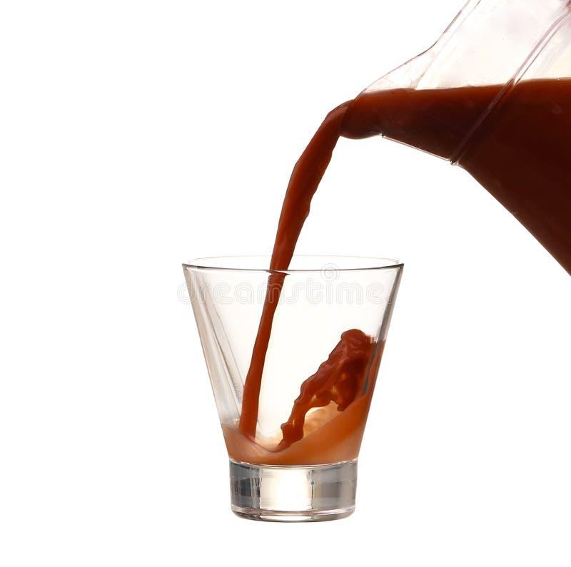 Chapoteo del chocolate con leche sobre blanco imagen de archivo