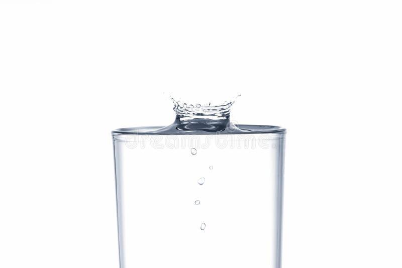 Chapoteo del descenso del agua sobre el vidrio de consumición en el fondo blanco imagen de archivo libre de regalías
