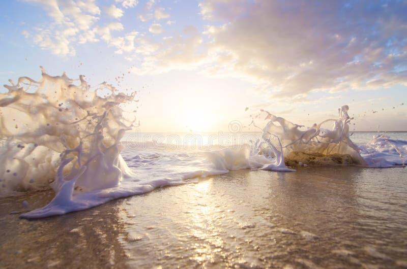 Chapoteo del mar en la puesta del sol foto de archivo