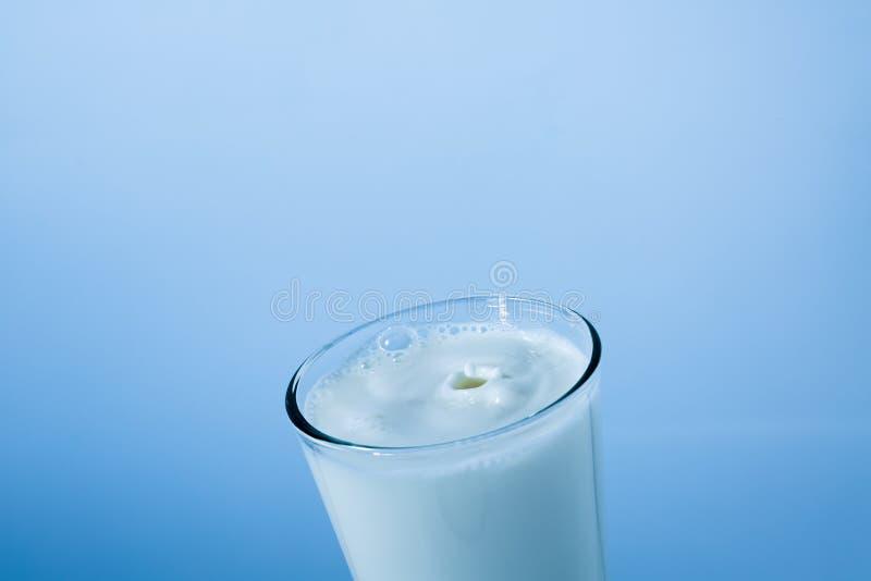 Chapoteo del vidrio de leche en fondo azul imagenes de archivo
