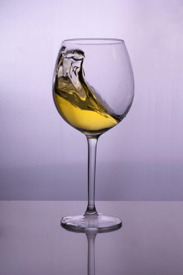 Chapoteo del vino blanco en un vidrio imagenes de archivo