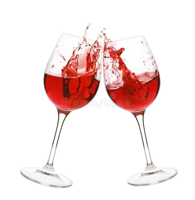 Chapoteo del vino rojo en dos vidrios imagen de archivo