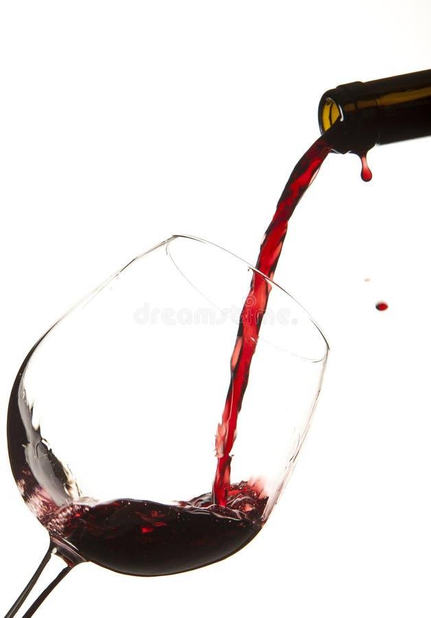 Chapoteo del vino rojo sobre un vidrio fotos de archivo