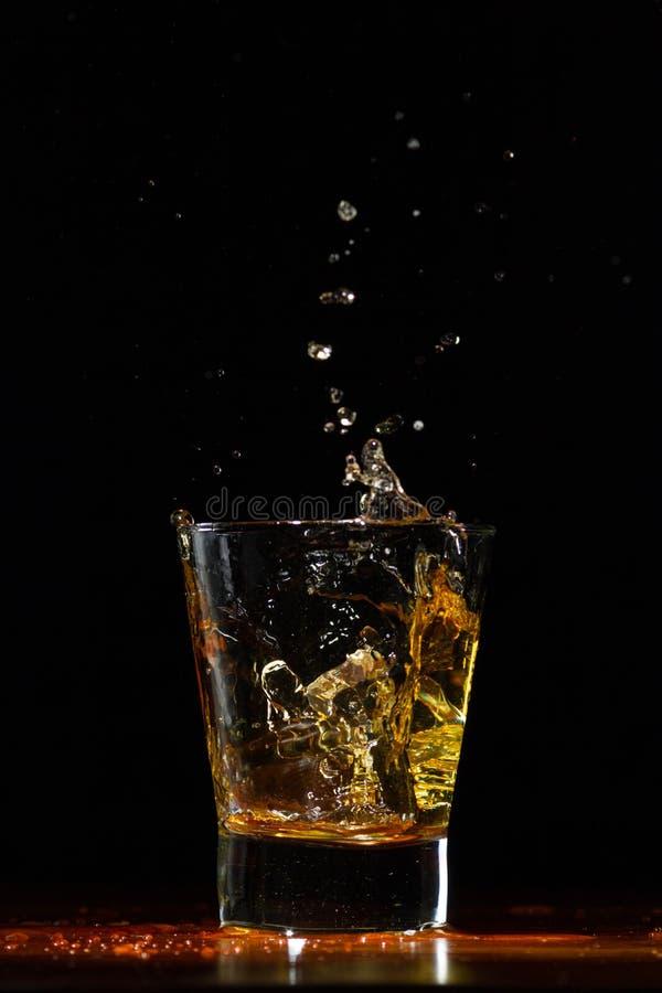 Chapoteo del whisky en vidrio en negro imagen de archivo